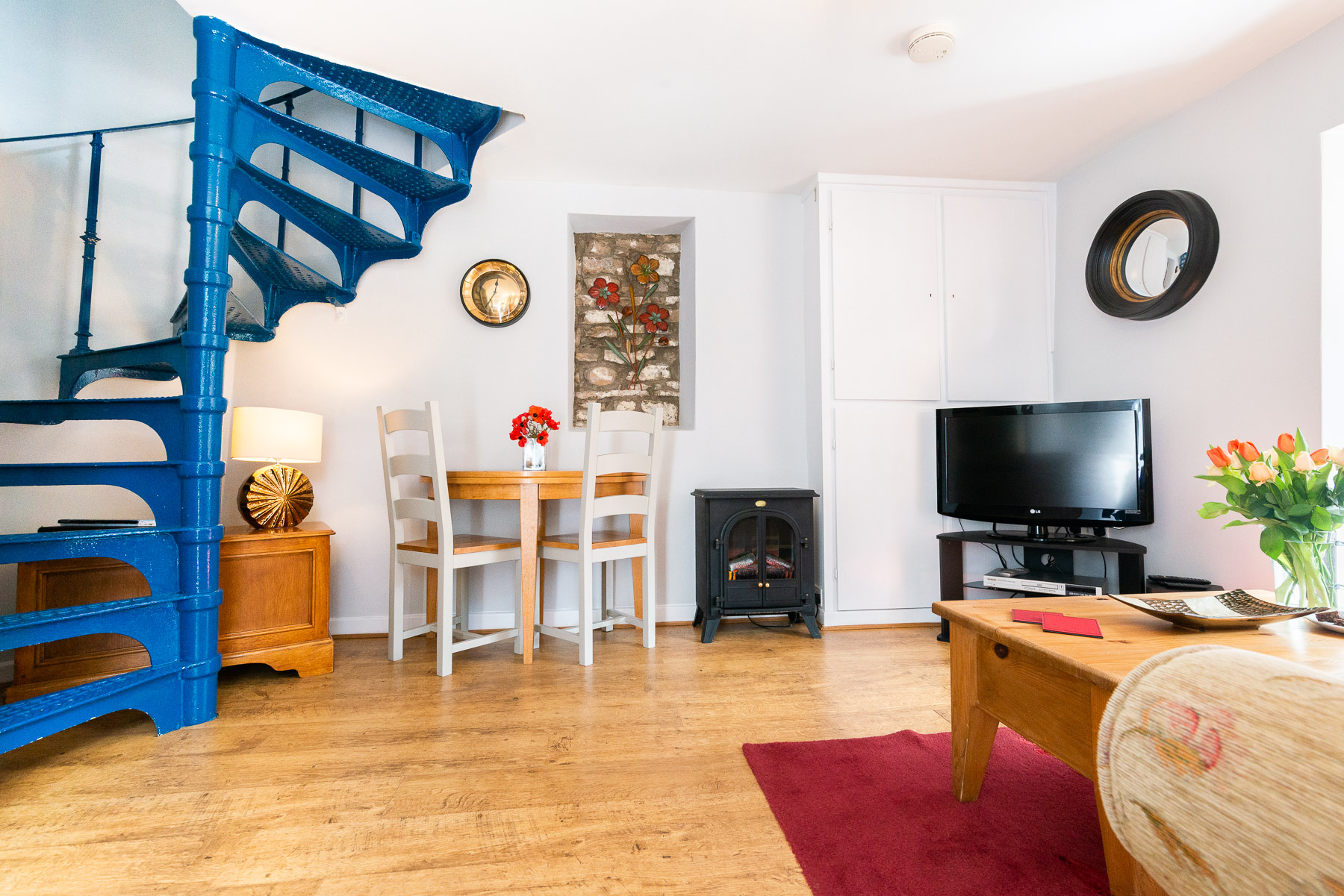 Courtyard Cottage Lounge with spiral stairs. A pet friendly holiday cottage.